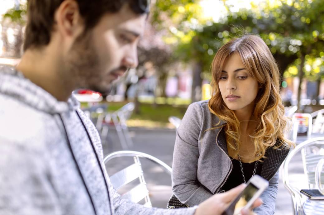 Eine Frau späht auf das Handy ihres Freundes