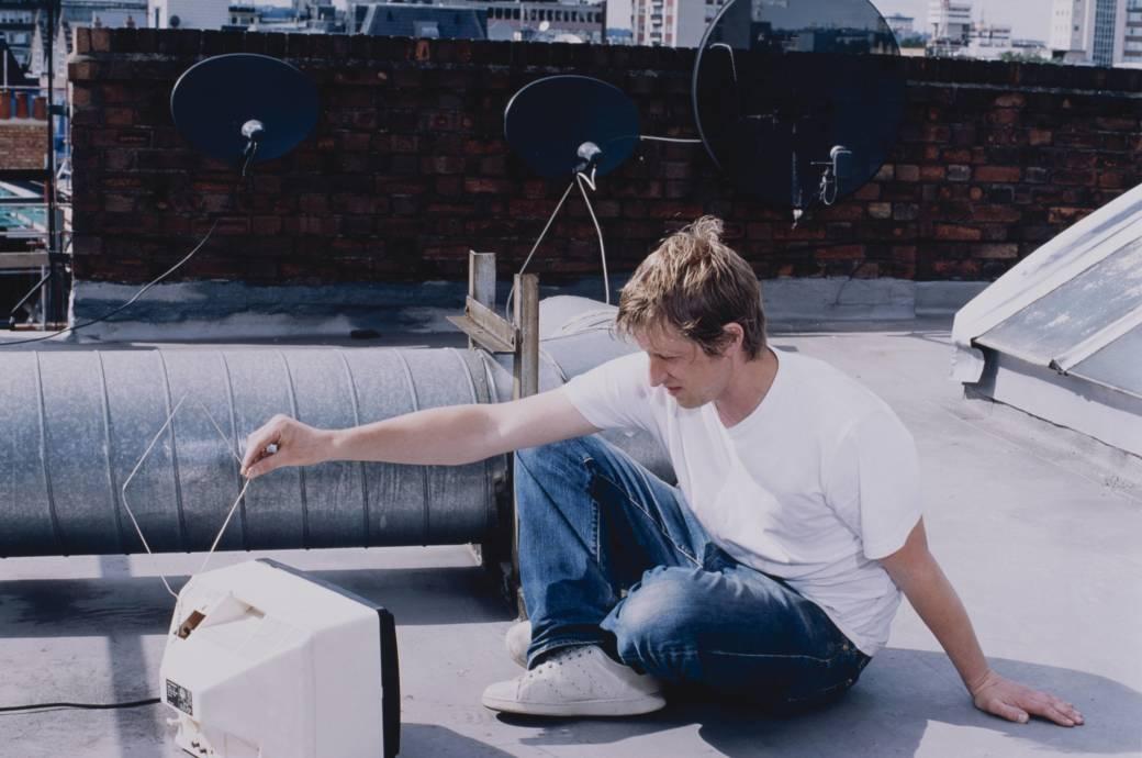 Mann sitzt auf dem Dach mit einem Fernsehgerät, im Hintergrund sind Satellitenschüsseln