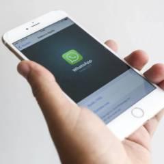 Hand hält Handy, auf dem WhatsApp zu sehen ist