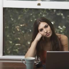 Frau sitzt gelangweilt vor ihrem Laptop