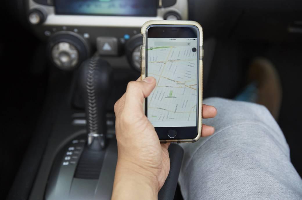 Mann hat Smartphone mit Navigations-Karte in der Hand