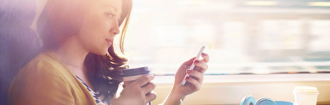 Frau sitzt im Zug und hält ein Handy in der Hand