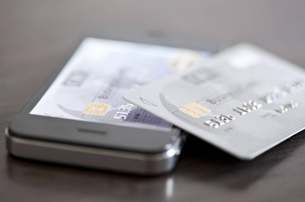 Ein Smartphone und eine Kreditkarte liegen auf einem Tisch