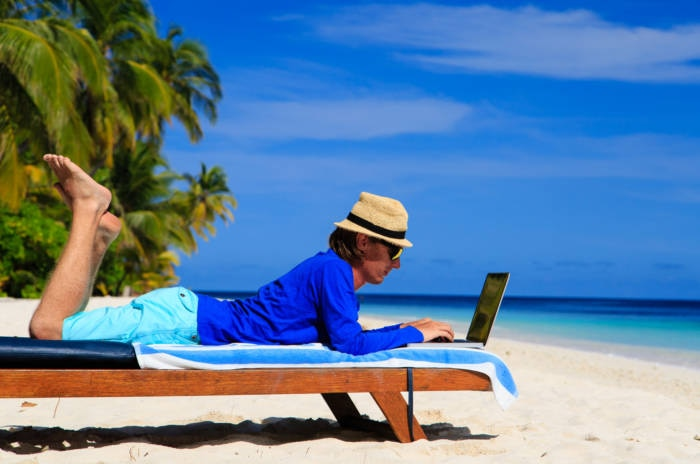 man with laptop on tropical beach