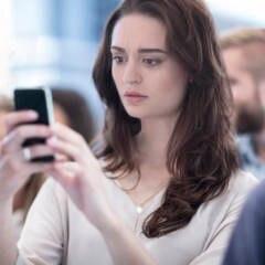 Frau schaut verunsichert auf das Handy.
