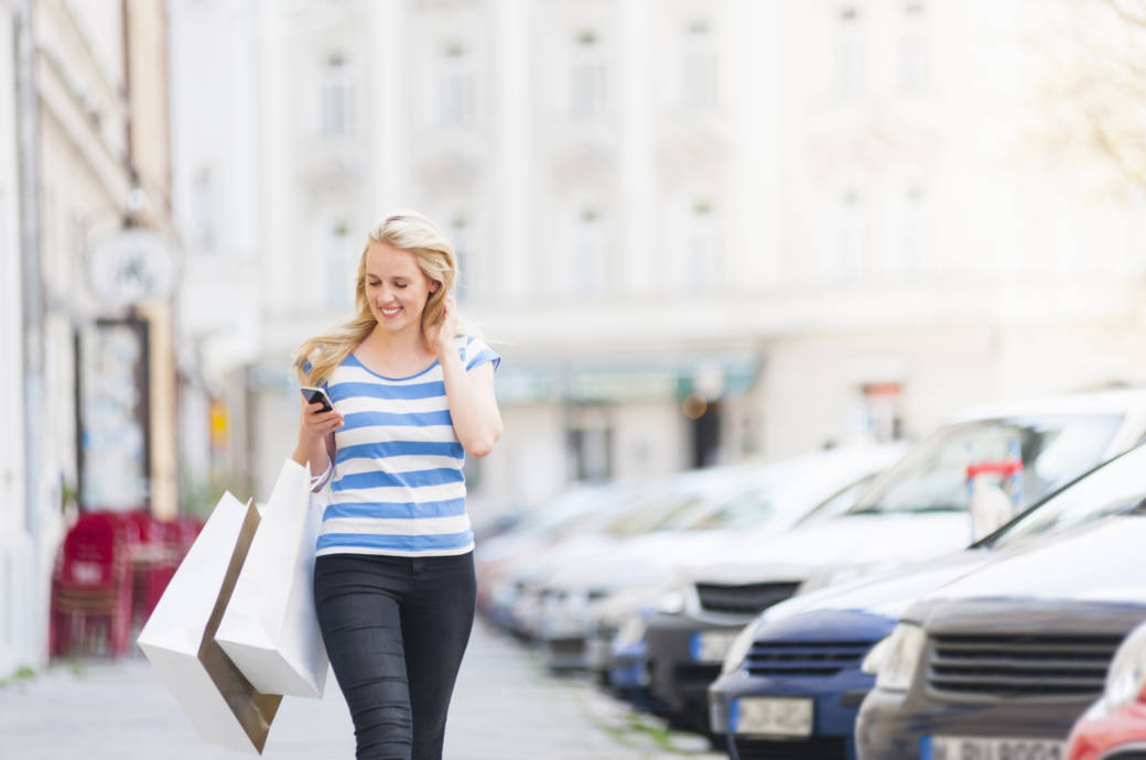 Frau läuft auf der Straße und schaut dabei auf ihr Handy.