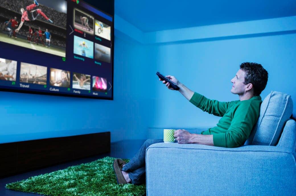 Mann schaut Fernsehen und benutzt die Fernbedienung.
