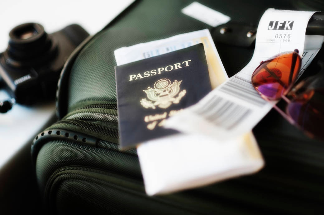 Reisepapiere und Sonnenbrille auf Koffer