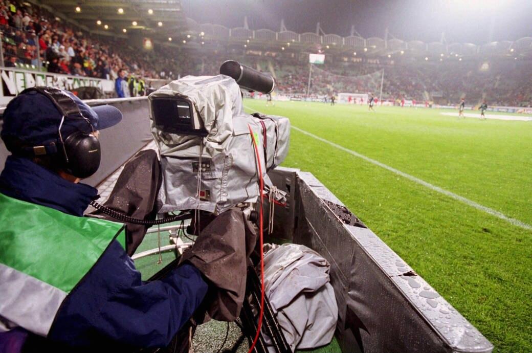 Kameramann mit Kamera neben einem Fußballfeld