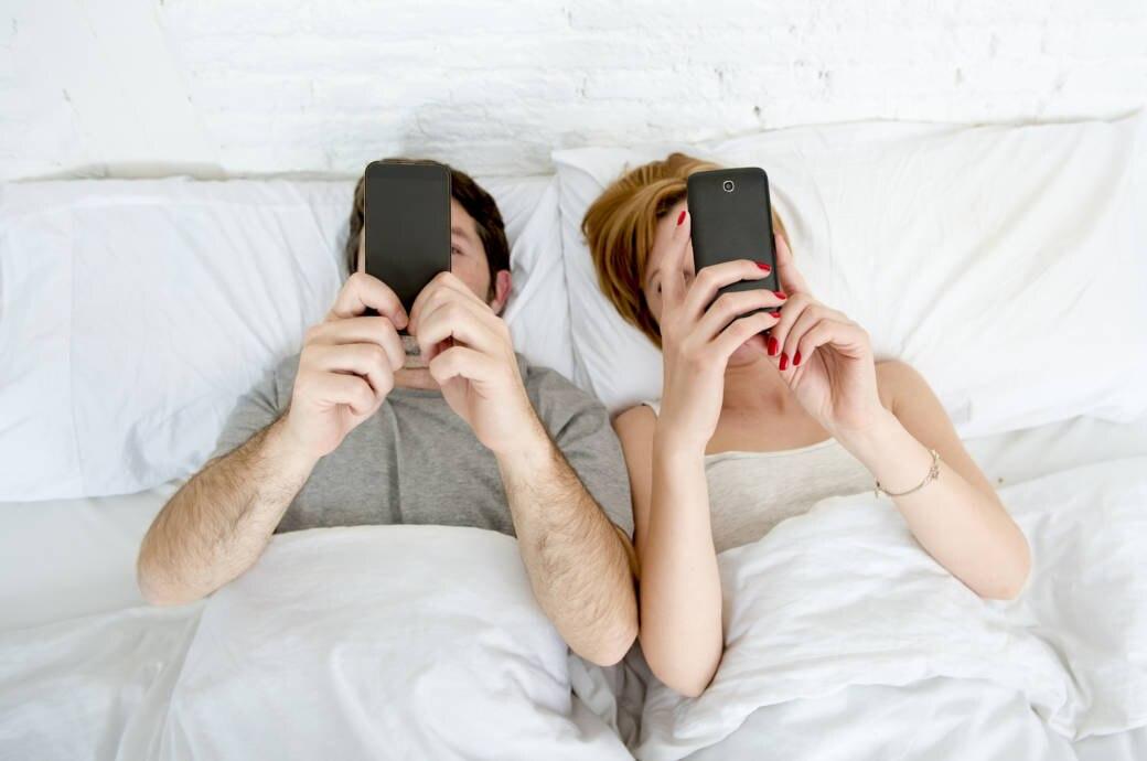 Ein Pärchen liegt im Bett. Beide halten ein Smartphone in den Händen
