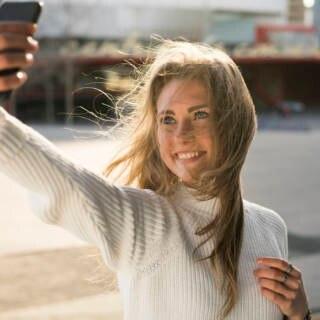 Eine junge Frau schießt im Sonnenschein ein Selfie