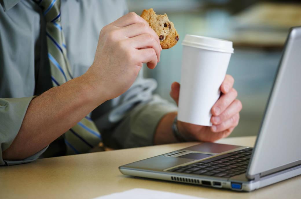 Mann mit Keks und Kaffee vor dem Laptop