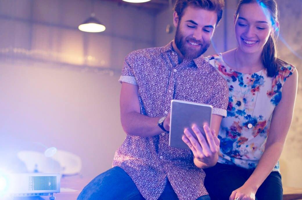 Mann und Frau mit Beamer und Tablet