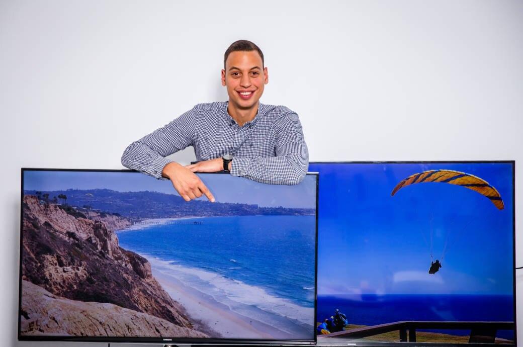 Hübscher Mann hinter Fernsehgeräten