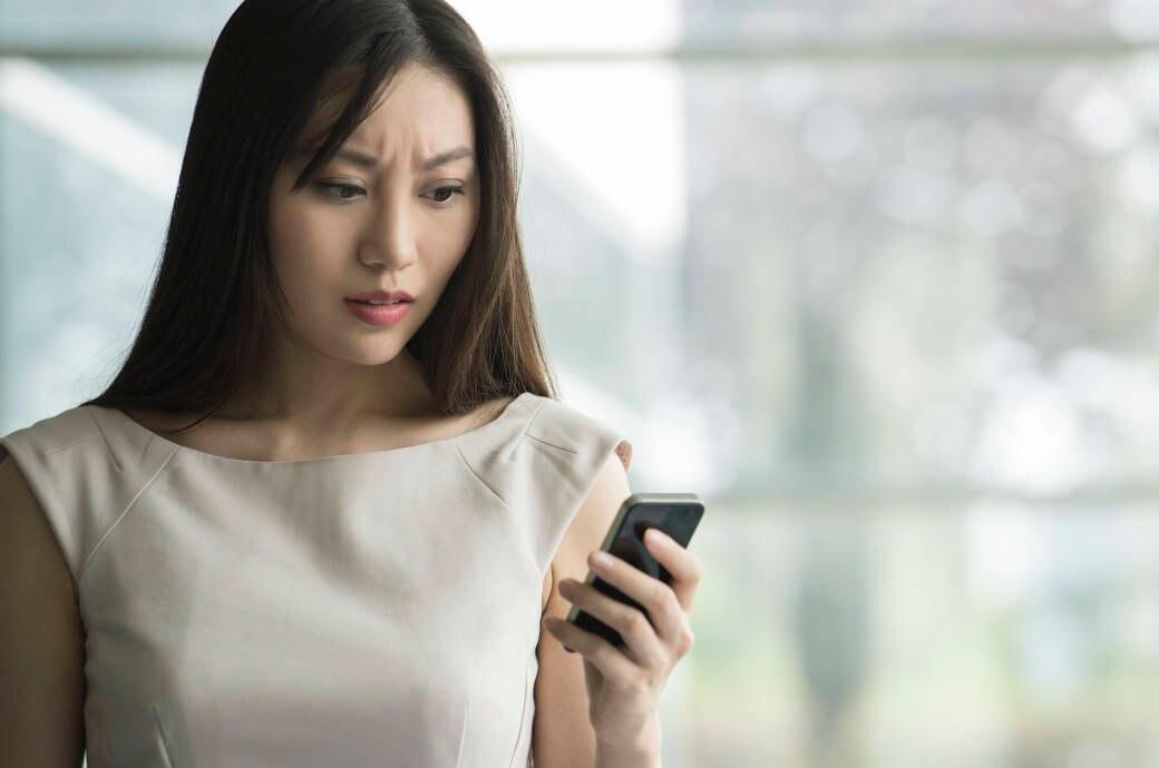 Frau schaut schockiert aufs Handy