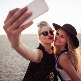 Zwei frauen stehen am Strand und machen mit ihrem Smartphone ein Selfie