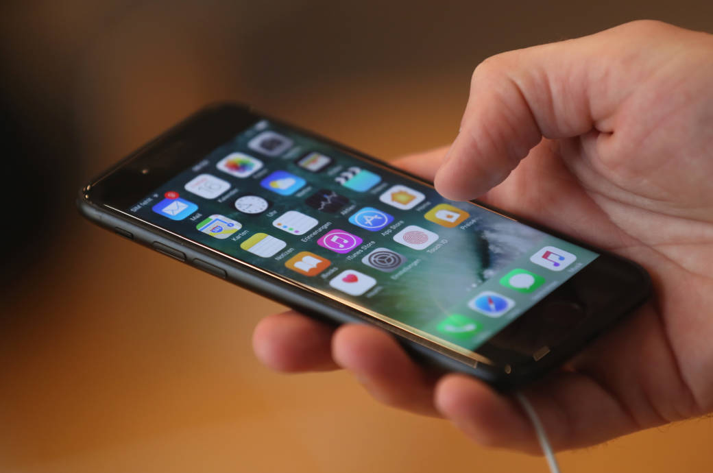 Eine männliche Hand hält ein Smartphone in der Hand