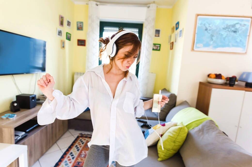 Junge Frau trägt Kopfhörer und tanzt