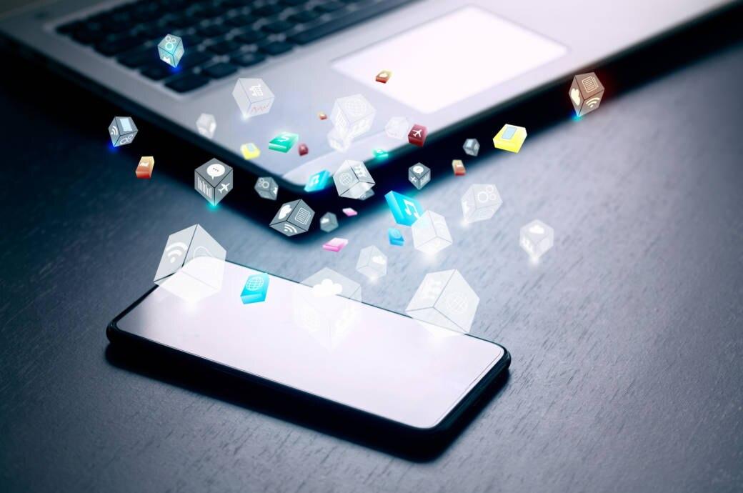 Smartphone und Laptop auf einem Tisch mit zahlreichen Apps