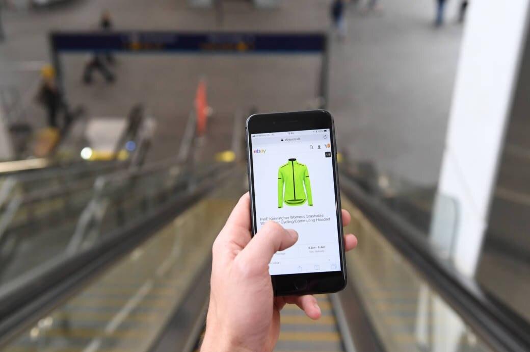 Mann auf Rolltreppe hält Smartphone mit geöffneter Ebay-Seite / Man on escalator holding Smartphone which shows ebay website