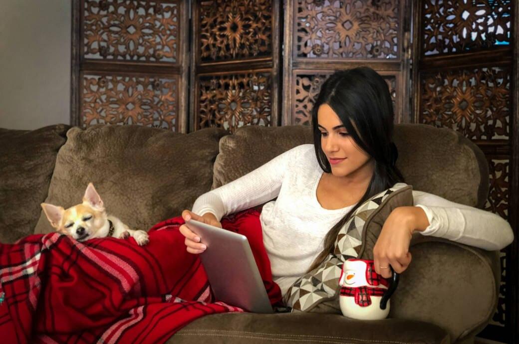 Frau mit Tablet und Hund auf Sofa