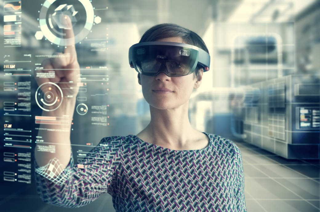 Frau mit Microsoft HoloLens hinter projiziertem Bildschirm