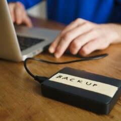 Mann macht Laptop-Backup auf externer Festplatte