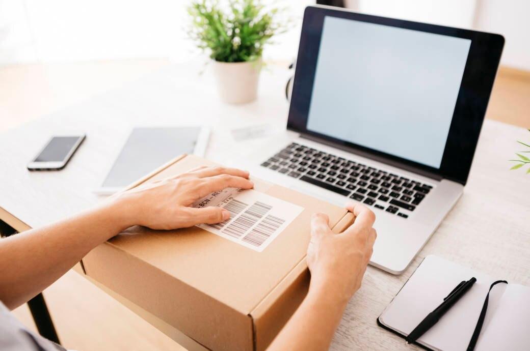 Frau mit Laptop und Paket auf Schreibtisch