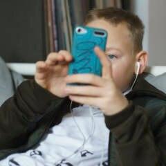 Junge liegt auf dem Bett und hat ein Handy in der Hand und hört Musik