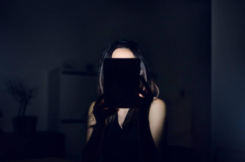 Frau hält Tablet vor Gesicht im Dunkeln