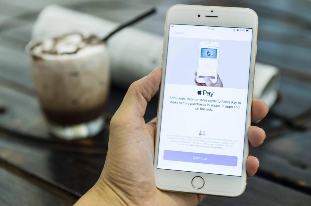 Hand hält Handy auf dem Apple Pay zu sehen ist