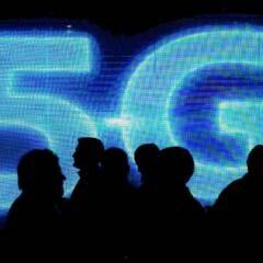 Menschen stehen vor einem 5G-Logo