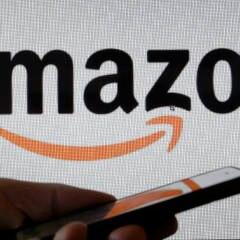 Hand hält Handy vor einem Amazon-Logo
