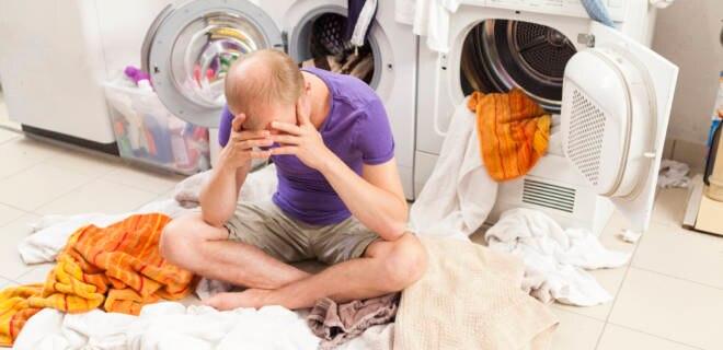 Mann sitzt auf Wäschhaufen neben Waschmaschine