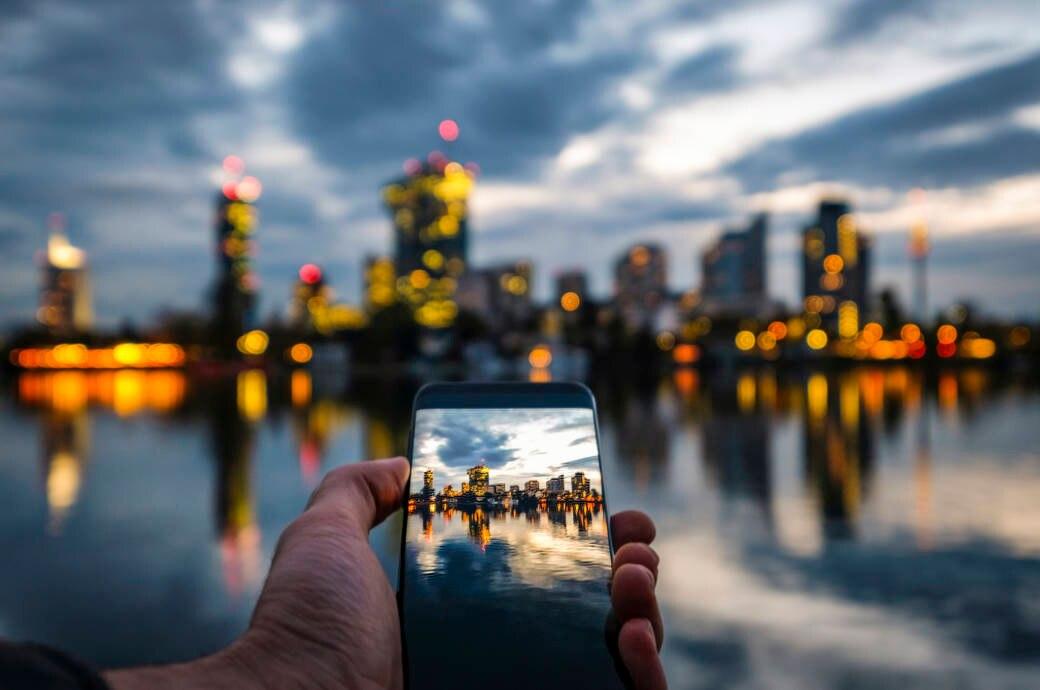 Mann hält Smartphone in der Hand, auf dem Display sieht man die Skyline von Wien