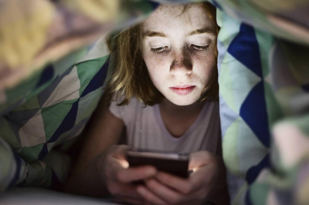 Kind mit Handy unter der Decke