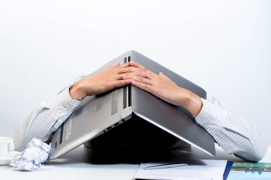Mann versteckt sich unter Laptop