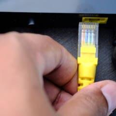 Person zieht Netzwerkstecker aus einem Router
