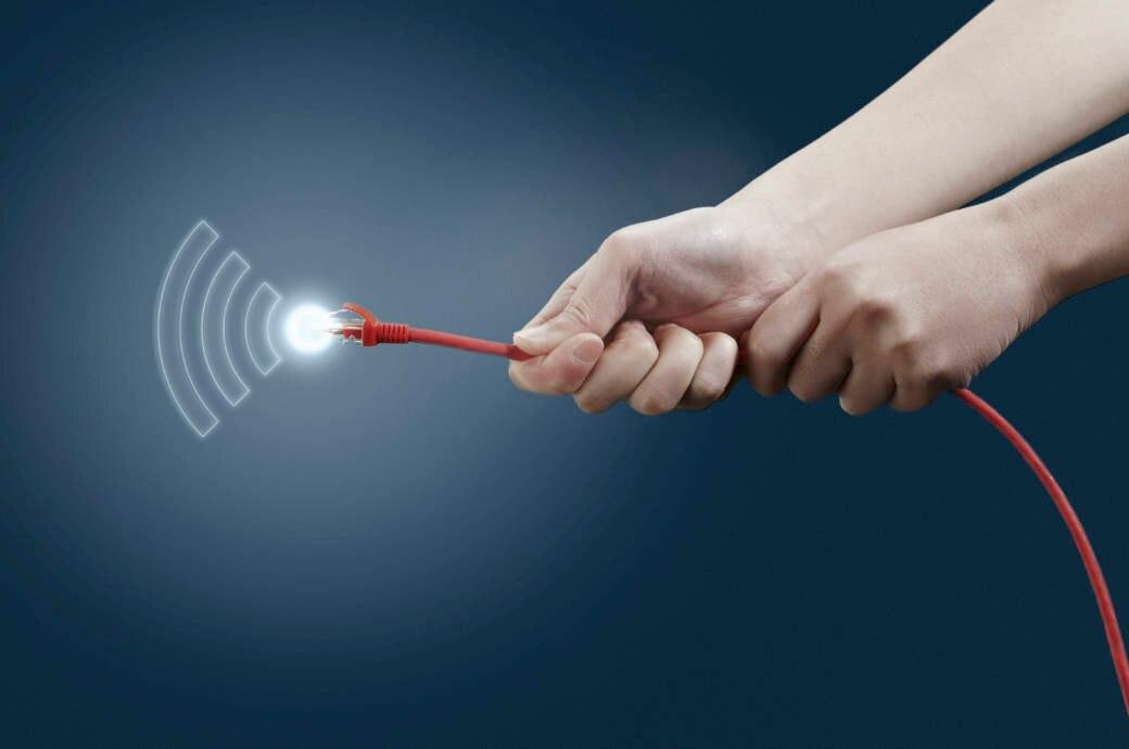 Mensch hält LAN-Kabel, aus dem WLAN-Signale kommen