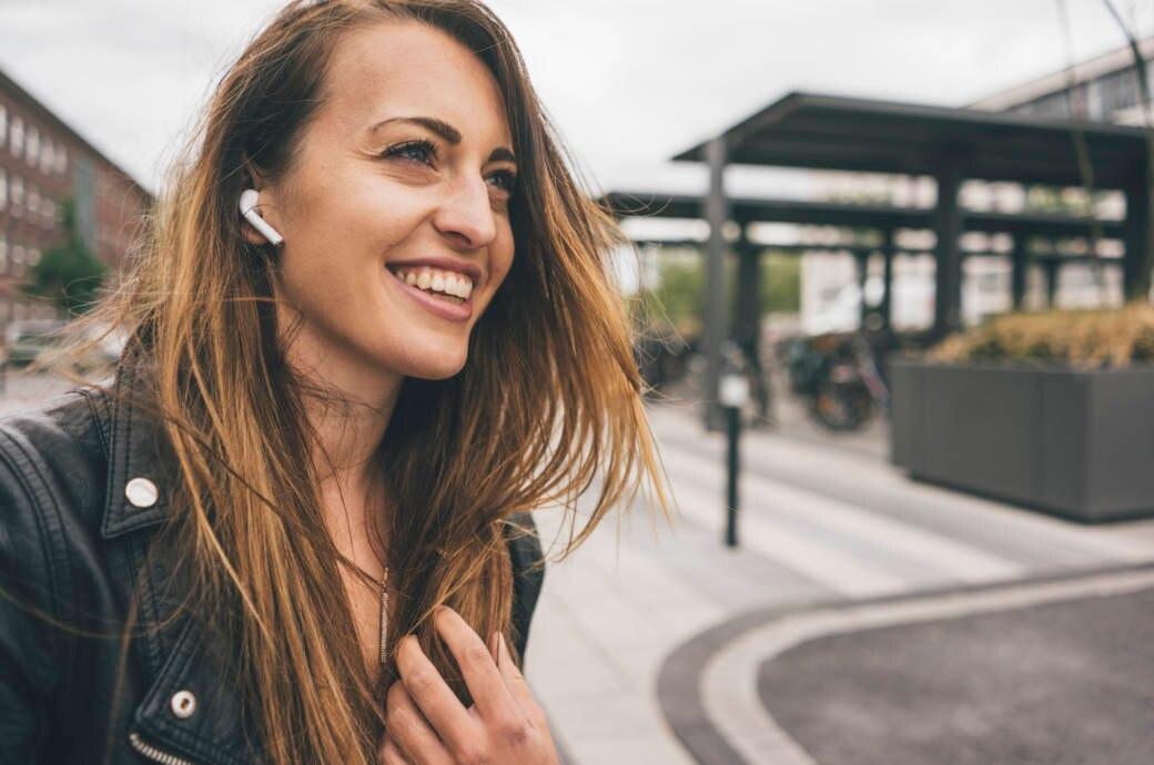 Lächelnde junge Frau trägt Apple AirPods