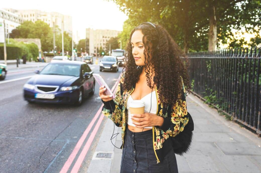 Frau trägt Kopfhörer und hält ihr Handy an einer Straße in der Hand