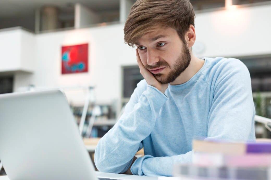 junger Mann schaut unglücklich auf seinen Laptop