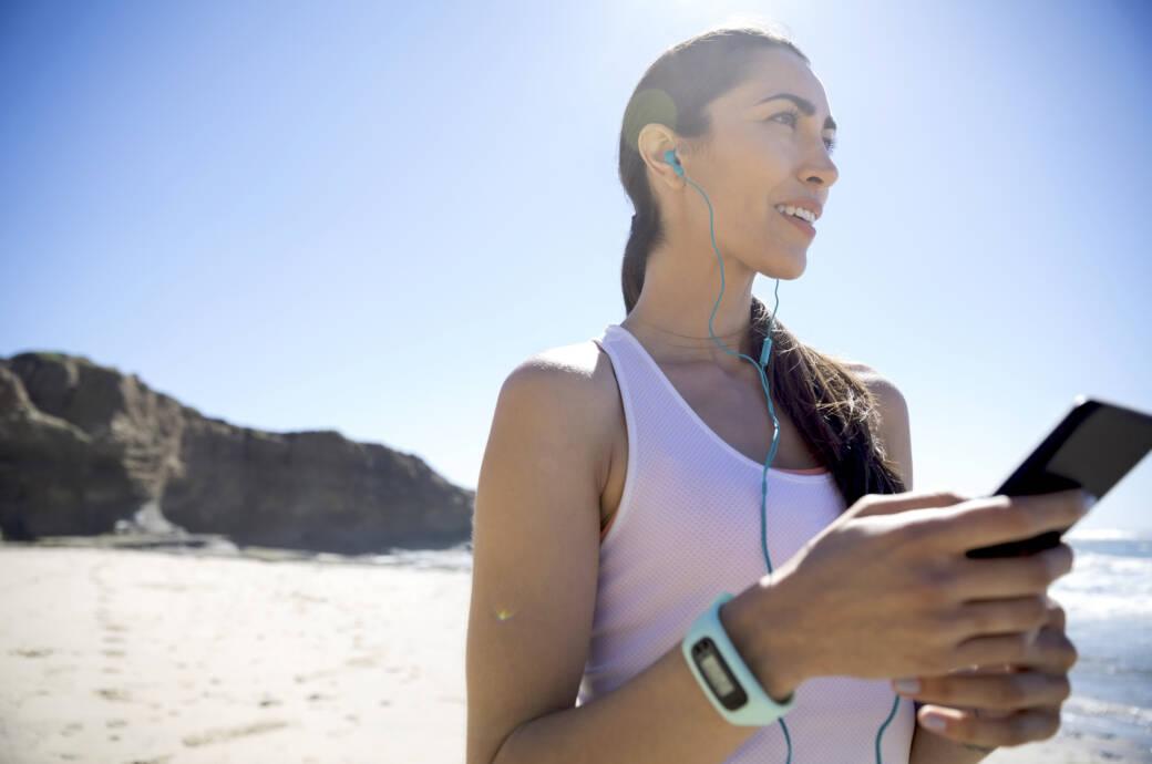 Eine junge Frau am Strand mit einem Fitnesstracker