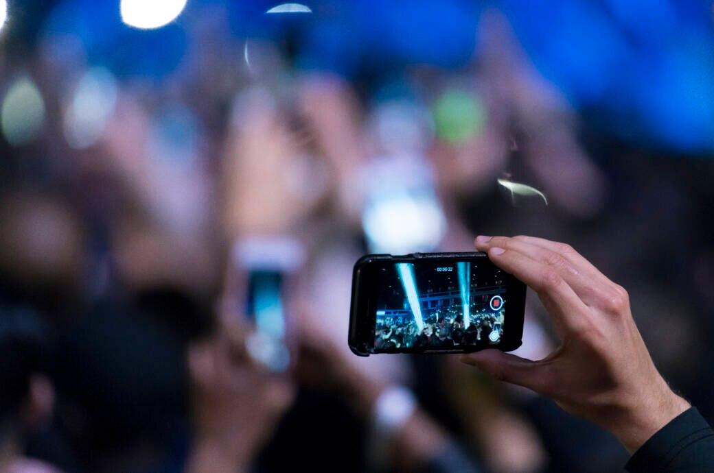 Hand filmt mit iPhone auf Event