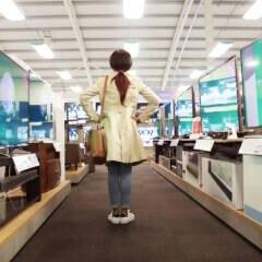 Frau im Elektronikmarkt vor Fernsehern