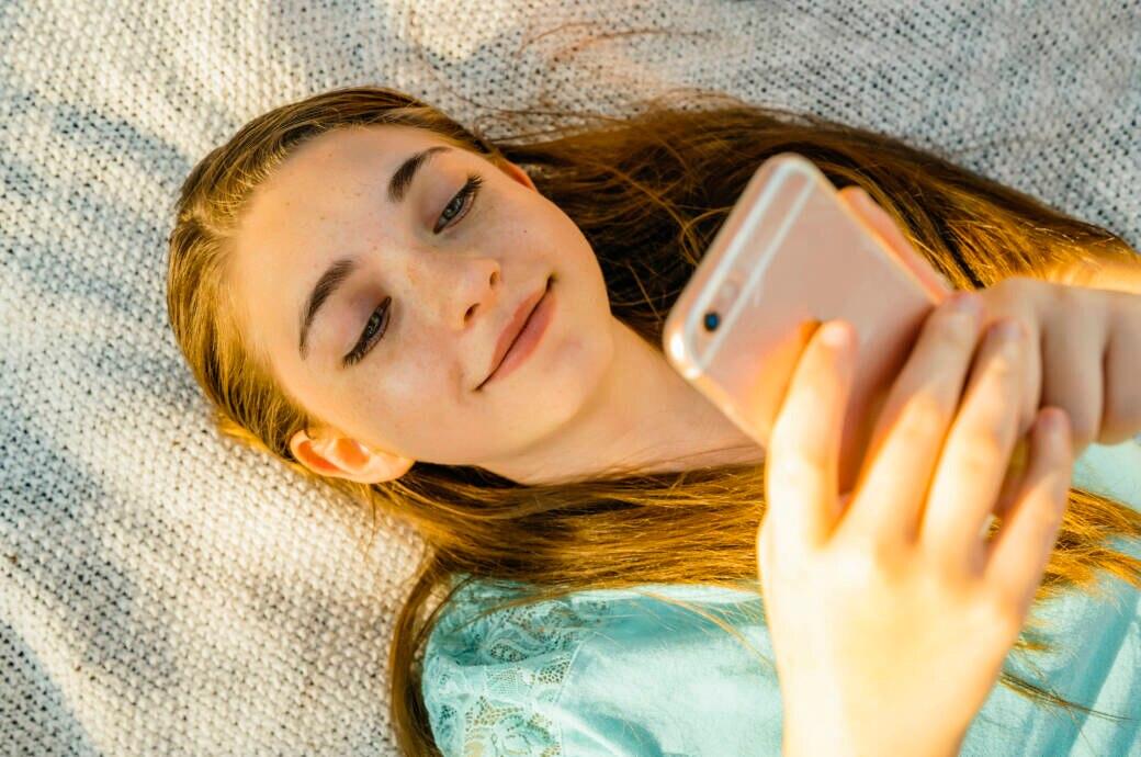 Mädchen liegt auf Decke und schaut auf ihr iPhone.