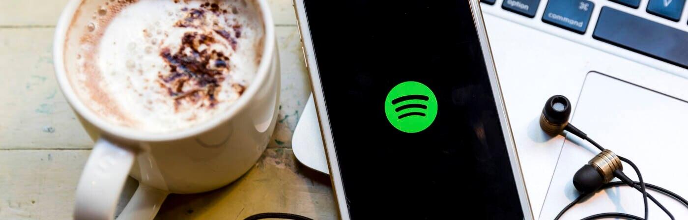 Smartphone mit Spotify-App, Kaffeetasse und Laptop