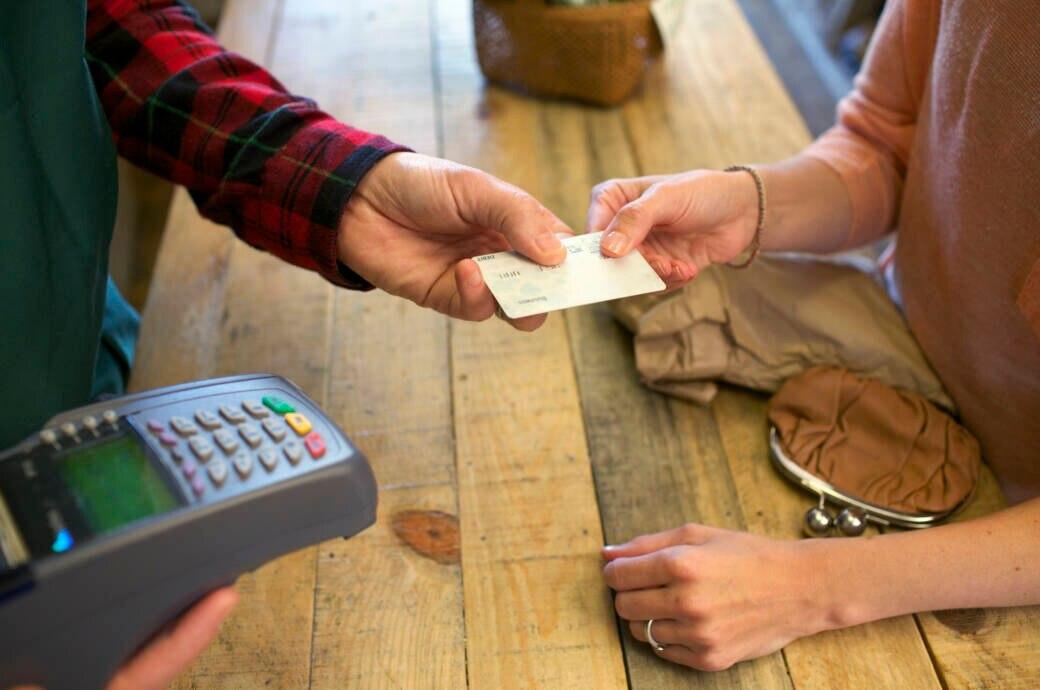Frau bezahlt mit EC-Karte an der Kasse