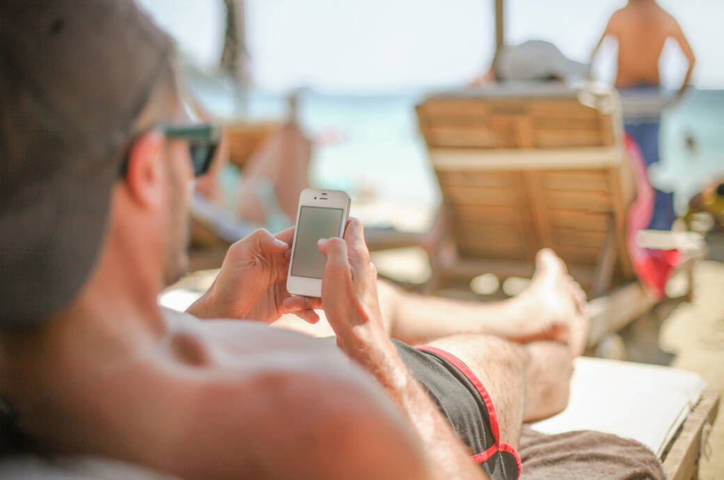 Ein Mann mit Basecap liegt auf Strandliege und schaut auf sein Smartphone