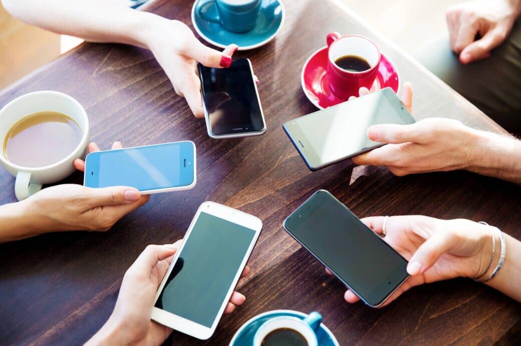 Mehrere Menschen sitzen mit Smartphones am Tisch